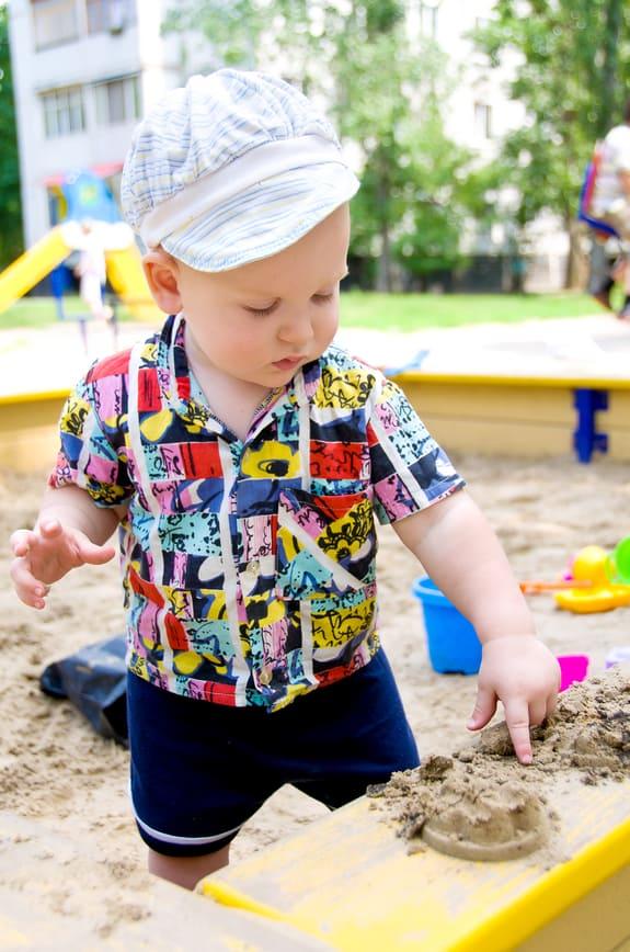 little boy playing outside in the summer children's sandbox